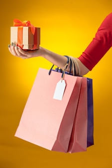 黄色の明るい買い物袋を持っている女性の手