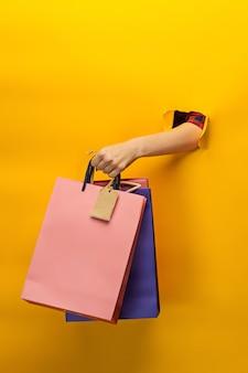 노란색에 밝은 쇼핑백을 들고 여성 손