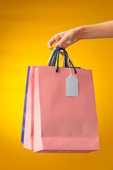 노란색에 밝은 쇼핑백을 들고 여성 손 프리미엄 사진