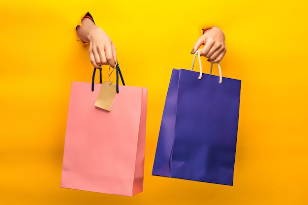 Female hand holding bright shopping bags on yellow through a torn paper