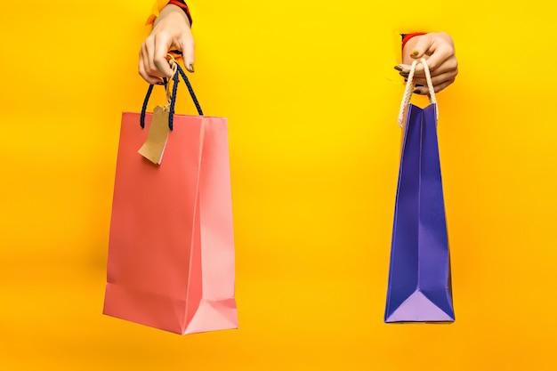 明るい買い物袋を持っている女性の手