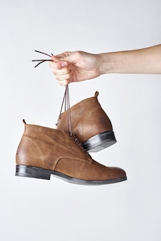 Female hand holding brown leather boots on shoeleces against white background