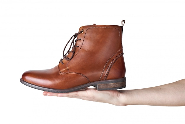 Female hand holding brown leather womens boot  on white background isolated