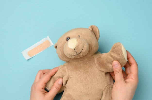 Female hand holding a brown teddy bear with a torn off eye, top view