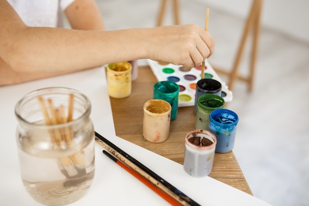 Женская рука держа кисть и углубляя его в краску. kid живопись с использованием акварели во время урока в художественной комнате.