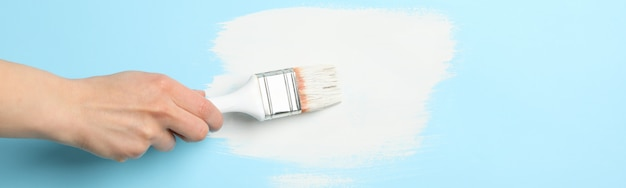 Female hand holding brush on blue background with white paint strokes