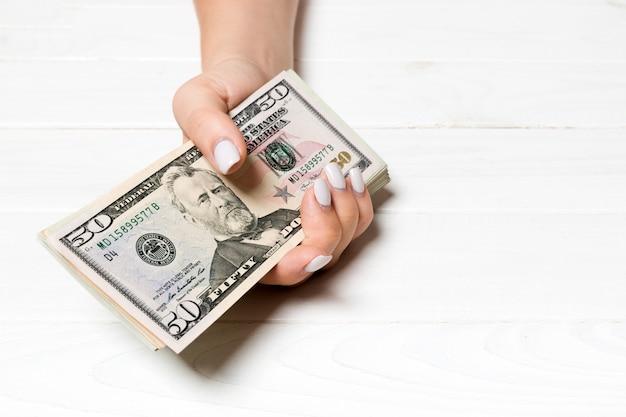 Female hand holding a bundle of money