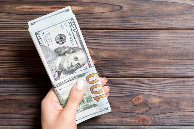 Female hand holding a bundle of one hundred dollar banknotes on wooden background. salary and wage concept with copy space