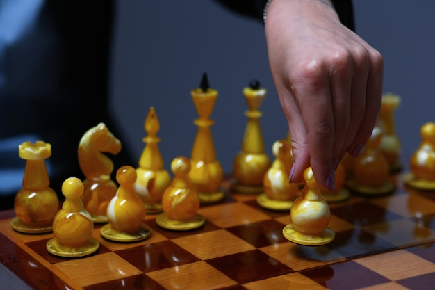 Female hand holding a business woman holding a chess piece.