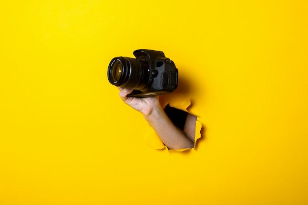 Female hand holding a camera on a bright yellow background