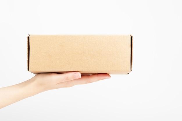 カートンボックスを持っている女性の手。食品の運搬。短納期サービス。