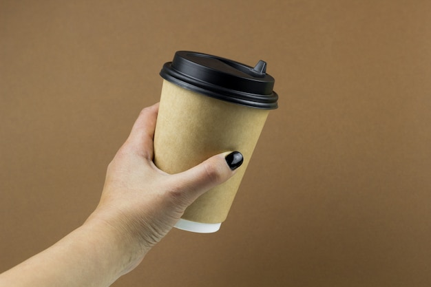 Female hand holding a ccoffee paper cup on brown background