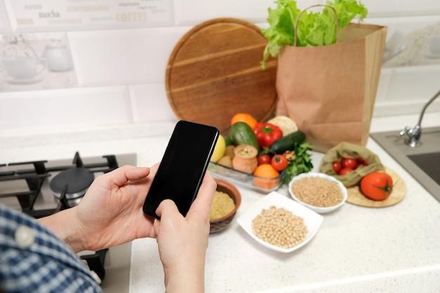 食料品の野菜と背景のキッチンテーブルに空の画面で携帯電話を持っている女性の手