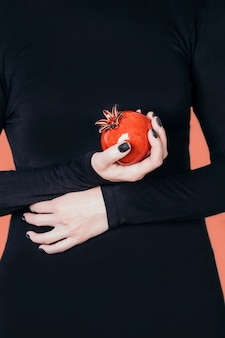 여성의 손을 잡고 세라믹 붉은 석류 열매, 검은 매니큐어와 매니큐어