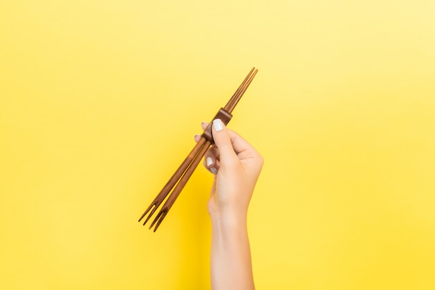 Female hand holding chopsticks. sushi concept with empty space
