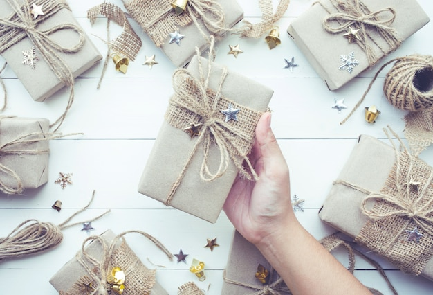 Female hand holding christmas presents gift box collection in vintage style
