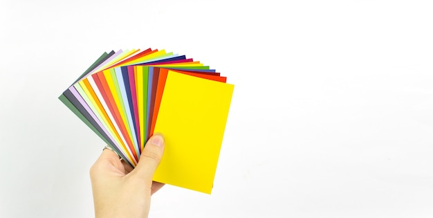 Female hand holding color of the year 2021 - illumanating. color trend palette. color trend palette. flat lay, top view.