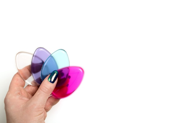 Female hand holding colorful silicone cosmetic sponges on a white background
