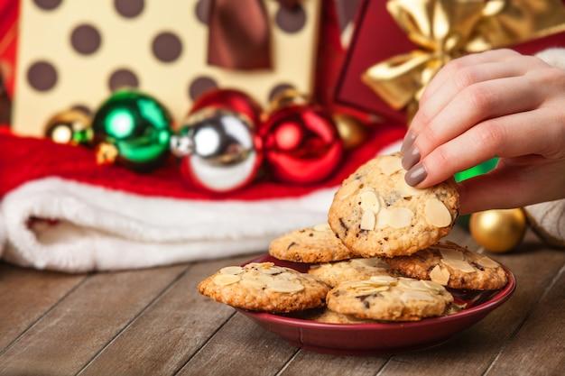 크리스마스 선물 배경에서 쿠키를 들고 여성 손
