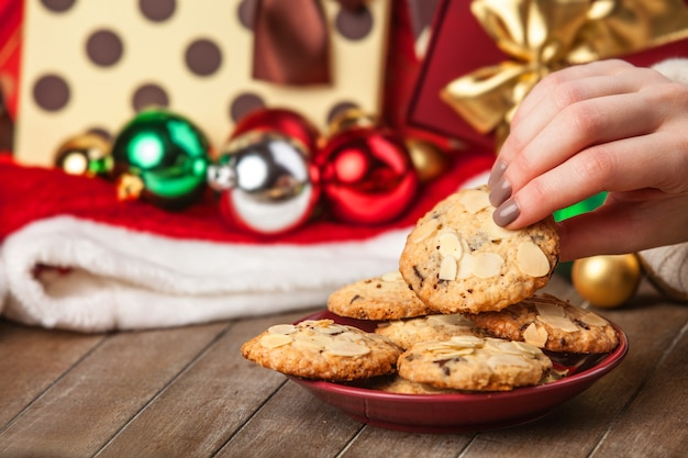 Female hand holding cookie at christmas gift background