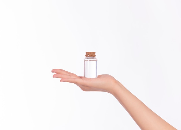 Female hand holding cosmetic bottle, retro style package with transparent liquor. micellar, tonic, alcohol, skincare and cure concept