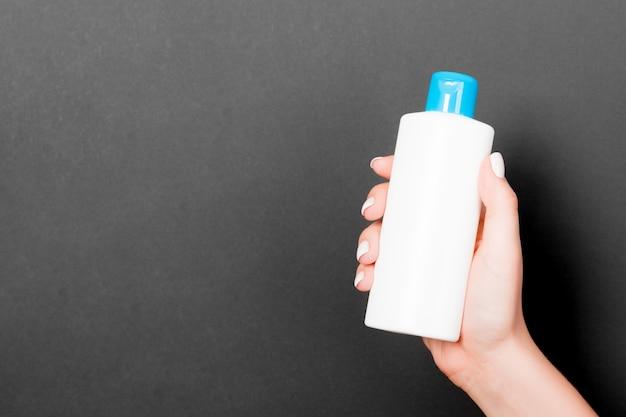 Female hand holding cosmetics bottle