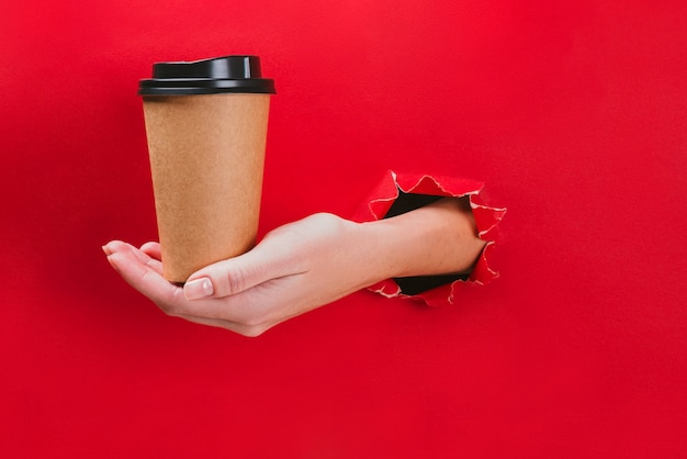 Female hand holding craft paper coffee cup through a hole in red.
