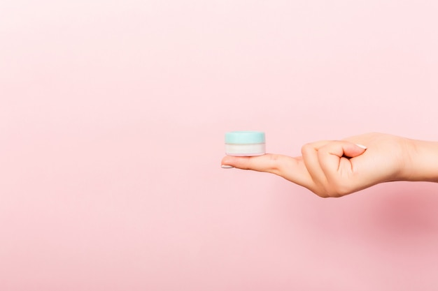 Female hand holding cream bottle of lotion isolated. girl give jar cosmetic products on pink background