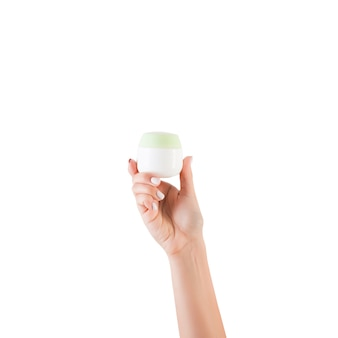 Female hand holding cream bottle of lotion isolated. girl give jar cosmetic products on white background