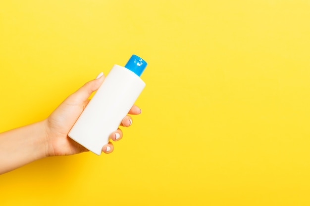 Female hand holding cream bottle of lotion isolated. girl give tube cosmetic products on yellow background.