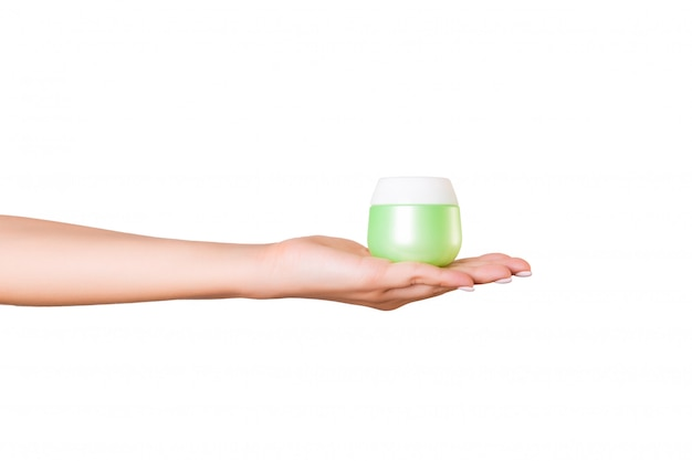 Female hand holding cream bottle of lotion isolated