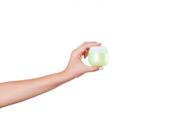 Female hand holding cream bottle of lotion isolated