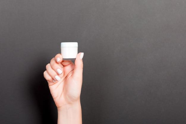 分離されたローションのクリームボトルを持っている女性の手。女の子は黒の背景に瓶化粧品を与える