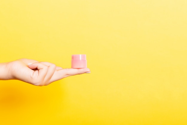 여성의 손을 잡고 격리 로션 크림 병. 소녀는 노란색에 항아리 화장품을 제공