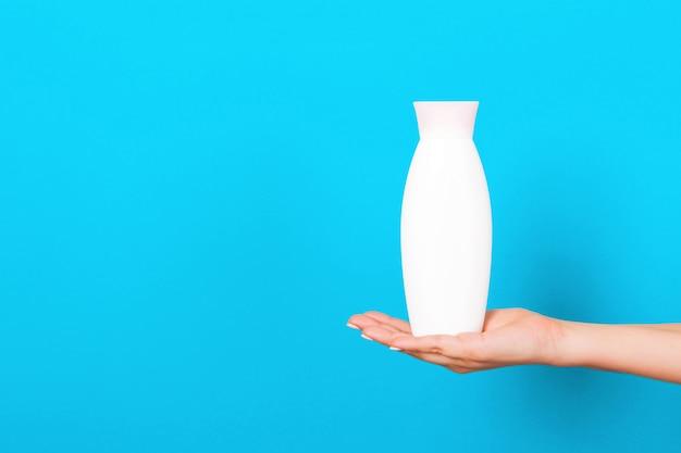 Female hand holding cream bottle