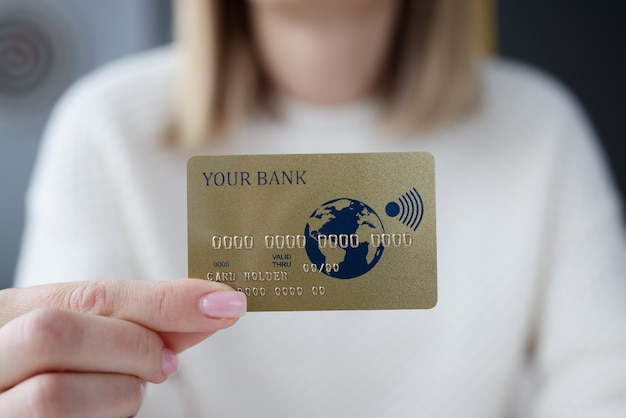 Female hand holding credit bank card closeup
