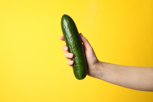 Female hand holding cucumber on yellow surface