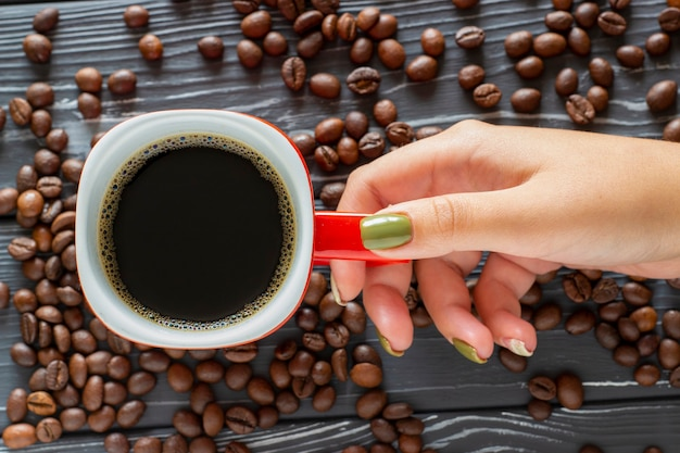Female hand holding a cup of coffee on a background of coffee beans lying on the table, top view.