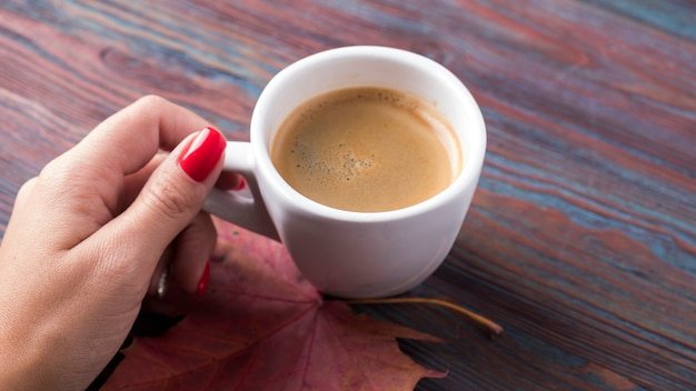 Female hand holding cup of coffee with autumn leaves on wooden background