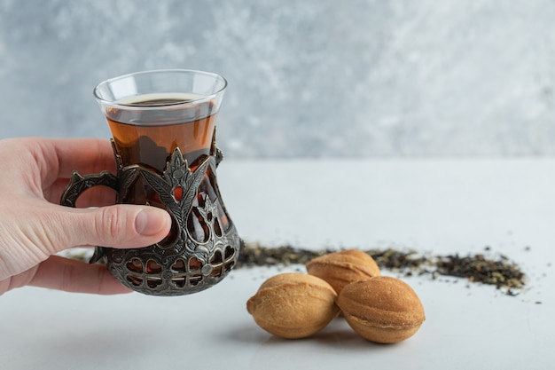 Female hand holding a cup of herbal tea with sweet walnut shaped cookie.