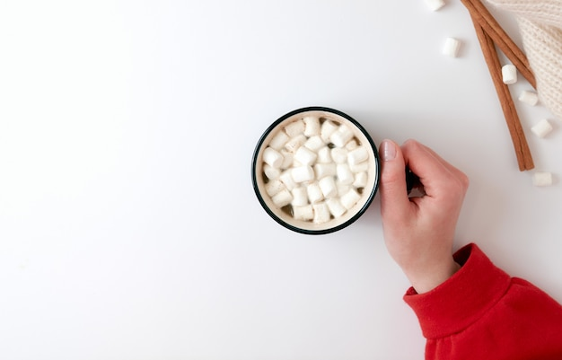 Female hand holding cup of hot chocolate with marshmallow