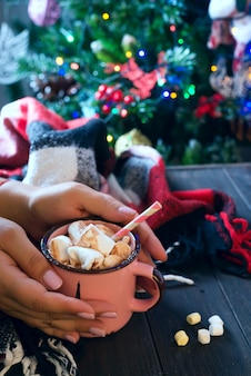 Female hand holding cup of hot cocoa or chocolate with marshmallow on wooden table above christmas tree