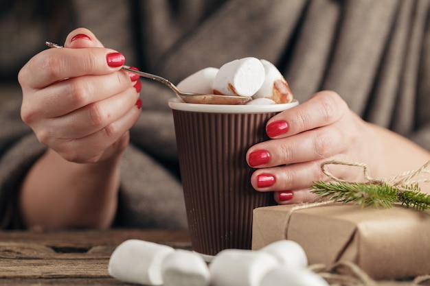 Female hand holding cup of hot cocoa or chocolate with marshmallow on wooden table