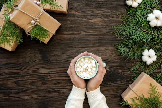 Женская рука держит чашку шоколада с зефиром и подарочные коробки на темных деревянных, вид сверху