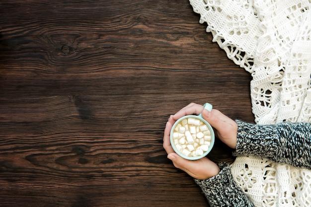 マシュマロとチョコレートのカップを持っている女性の手