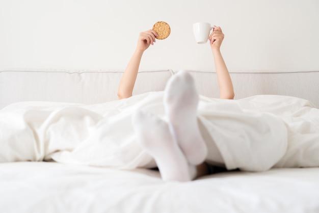 ベッドの毛布の下からコーヒーのカップを持っている女性の手。朝目を覚ます女性