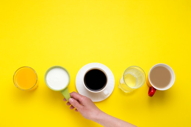 Female hand holding a cup with yogurt and beverages set orange juice, coffee with milk, black coffee, plain water, yoghurts on a yellow background. flat, top view