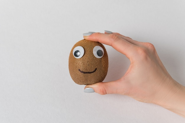 Female hand holding cute kiwi with googly eyes and painted smile. white background. kiwi character