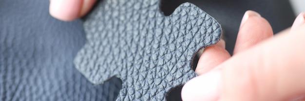 Female hand holding dark blue skin sample closeup
