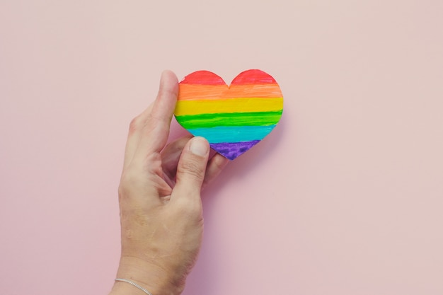 Female hand holding decorative heart with rainbow stripes